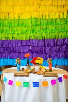 Pinata fringe backdrop. DIY by folding and cutting plastic party table cloths and tape in layers on wall.  Great and inexpensive idea!