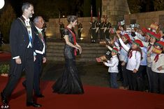 Spain's King Felipe, left, Queen Letizia, and Portuguese President Marcelo Rebelo de Sousa react to children waiving flags of both countries as they arrive for a gala dinner