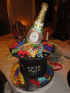 Top hat made with 4- 8in cakes covered in fondant. Gumpaste bottle and pocket watch. Fondant confetti!