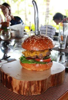 The Beef Burger from @Four Seasons Resort Mauritius at Anahita is a meal in itself. Recreate this feast at home: 1 sesame seed burger bun, 200g minced beef burger, 10g mayonnaise, 20g lettuce, 15g onion ring, 15g sliced green cucumber, 32g sliced tomato, 1 slice (28g) of American cheese.