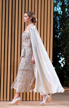 Gigi Hadid wears a dress and cape in the spring 2016 Chanel couture show