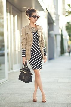Toss a light rain jacket over a chic, striped dress.  Pull up your hair for a fuss-free, ladylike look.