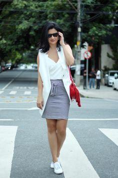 Look do dia Constanza Fernandez: saia listrada, com blusinha branca e colete branco, básico, atemporal porém estiloso ao mesmo tempo.