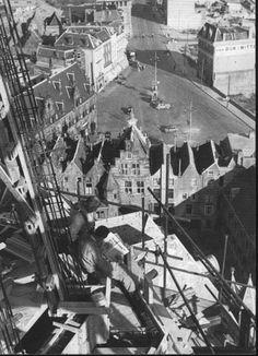 Bouwvakkers lezen een krantje op een steiger tijdens de wederopbouw van de Sint-Stevenstoren. Op de achtergrond de Grote Markt. De foto is gemaakt omstreeks 1950.