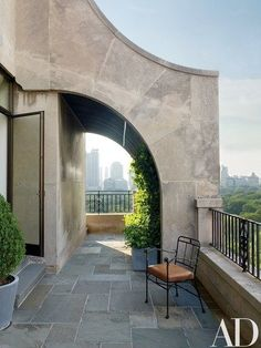 On the bluestone terrace, Diego Giacometti's lion chair meets zinc planters custom made by Edmund D. Hollander, who also designed the plantings | archdigest.com