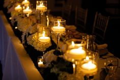 Head table decor.  White hydrangea, roses and peony centerpiece with pedestal candles.