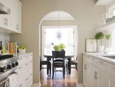 All white galley kitchen opens up to dining room