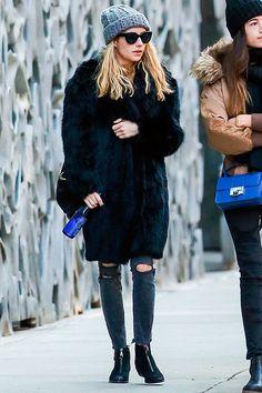 Street style look Emma Roberts usando maxi casaco pêlos preto, calça rasgada, bota cano baixo, gorro cinza e maxi óculos de sol.