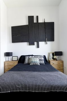 "Sneak Peek: A Modern Chicago Home. ""Above our bed is another Frank Girard abstract. This one was hanging outside at my grandparents home for years so is a bit ""rustic."" The black and white throw blanket and pillows are IKEA, as are the nightstands which I stained and updated with Anthropologie knobs. The lamps originally had white shades I painted black and the bases I made from fabric."" #sneakpeek"