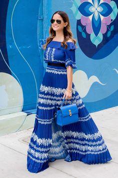 Jennifer Lake Style Charade walking in a blue pleated Self Portrait maxi dress, and blue Henri Bendel bag at a blue street art mural wall