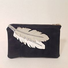 This black leather pouch was created from a leather jacket. The feathers are made of white and off-whit leather and attached by stitching. The