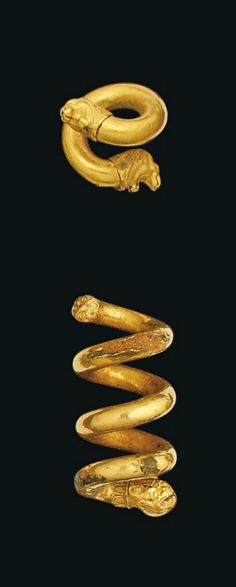 A GREEK GOLD SPIRAL EARRING   CLASSICAL PERIOD, CIRCA 5TH CENTURY B.C.   Composed of sheet gold over a bronze core, with one and a quarter turns with lion head terminals, with open jaws and naturalistically modelled mane, 5/8 in. (1.5 cm.) long; and another with three and a half turns, sheet gold over a bronze core, possibly a hair ring, with female head terminal, the other terminal in the form of a rosette with central grain, 1½ in. (3.8 cm.) long