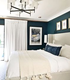 Bedroom with dark blue walls and white and Ivory bedding #bedroomideas #darkwalls