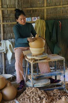 A young Cambodian woman creates a clay pot using a pottery wheel in Kampong Chhnang province, Cambodia.