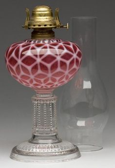 "COBWEB EASON-FORM STAND LAMP, cranberry opalescent font, colorless notched and prism base, No. 2 Taplin-Brown collar with patent information, period slip burner and non-period chimney.  9 1/4"" h to top of collar, 5 1/4"" dia base. <BR><I>Polishing to underside of foot, otherwise undamaged.</I><BR>Literature: Base as Thuro I, p. 237, bottom row, No. 4. Font parallels Thuro II, p. 101l.<BR> Provenance: From the collection of Larry & Diana Nellans.<BR>Catalogue Notes: An extremely rare and…"