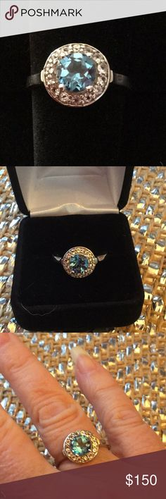 Genuine Electric Blue Topaz Halo Ring What a stunning blue,  sparkles are just fabulous, similar to a blue diamond I The Halo of Crystal White Topaz that embraces the genuine Blue Topaz is spectacular.  The setting is .925 silver and the side gallery allows more light in to add to the sparkle Atlanta Estate Jewelry Rings