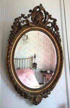 Miroir ovale en bois et stuc doré à décor central d'une coquille