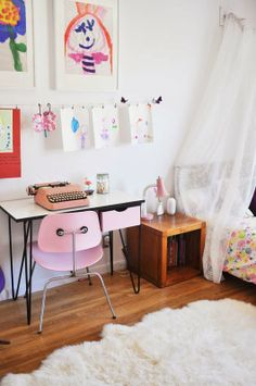 Pretty pink chair, hanging artwork on clothespins, vintage typewriter, white canopy = Heaven.