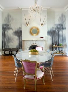 Mis-matched upholstered antique dining chairs with a modern marble saarinen dining table + crystal chandelier.