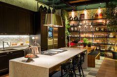 O papel de parede que imita tijolos de demolição reforça o clima rústico e industrial da cozinha gourmet de Alexandre Lobo e Fábio Cardoso