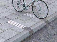 Des barrières pour accrocher les vélos cachées dans le sol. Gain de place, discrétion, sécurité.