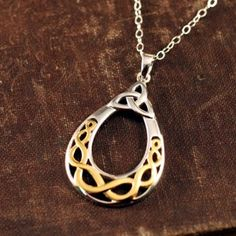 Our Celtic Knot Filigree Necklace in two silver and gold is boldly brilliant. The unbroken lines of the trinity knot combined with the unbroken lines of a woven Celtic knot are symbolic of life's journey.
