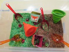 Apple sensory table-apple scented rice, acrylic apples, scoops, pails, and funnels