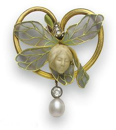 *AN ART NOUVEAU IVORY, DIAMOND AND ENAMEL BROOCH, BY HENRI VEVER   Designed as a carved ivory female face, enhanced by gray and green plique-à-jour enamel mistletoe, within a gold stemlike surround, suspending a bezel-set old European-cut diamond and freshwater pearl drop, mounted in gold, circa 1900, (with pendant hoops for suspension)  Signed Vever for Henri Vever, Paris