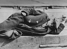 An unemployed man in an old coat lays on a pier in the New York City docks during the Great Depression, 1935