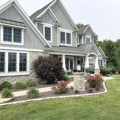 Grey Shingle style home. Board and batten. Mastic Shingle. Grey metal roof. Craftsman style home. Front porch with tapered columns. Home front elevation. Home exterior. Professional landscaping. @carolineondesign