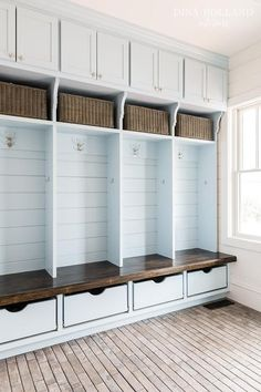Sky blue mudroom boasts blue built-in lockers adorned with Rejuvenation Pittock Double Hooks sandwiched between sky blue cabinets adorned with Schaub Symphony Knob w/Star Backplate in Polished Nickel fitted with shelves lined with wicker baskets on top and sky blue drawers sans hardware on bottom.
