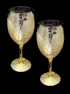 Angel Wings Wine Glasses-8oz. - This set of 2 wine glasses truly shimmer like angels wings. Each glass is hand painted in gold and silver accentuating the ethereal look of this heavenly design. This design will enhance the beauty of your dining room china. Proudly made in the USA!!
