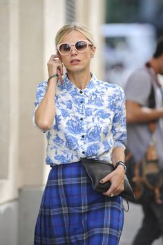 Shop this look on Lookastic:  http://lookastic.com/women/looks/sunglasses-dress-shirt-clutch-watch-skater-skirt/9555  — Pink Sunglasses  — White and Blue Print Dress Shirt  — Black Leather Clutch  — Silver Watch  — Blue Plaid Skater Skirt