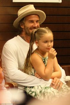 Proud papa: David Beckham sat with daughter Harper, six, on his lap as his son Brooklyn, 18, signed copies of his book at The Grove in Los Angeles on Wednesday night