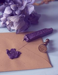 Wax seal wedding invitations. Takes a bit of practice to get it right, however I already have an 'A' seal we can use, we'd just need to buy some purple or lilac wax.