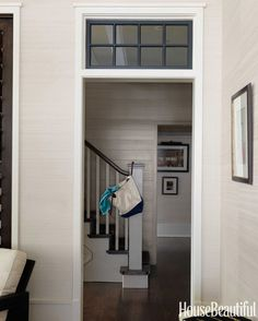 The entry's horizontal plank paneling, painted in Benjamin Moore Regal Select in Briarwood, contrasts with the living room's sunnier color, Knoll Textiles' Ovation.