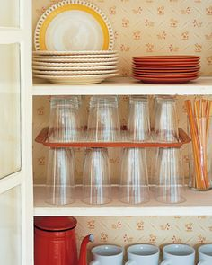 Great tip:  Use old serving trays as shelf dividers, doubling cupboard space.
