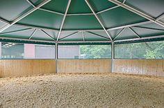 Innenansicht einer Longierhalle mit Holzbande