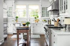 To update this kitchen, the homeowner and decorator Phoebe Howard installed hardwoods to match the rest of the house, swapped the dark black granite and tile for Carrara marble counters and backsplash tiles, changed the cabinet hardware, put in a movable island, and painted just about everything.    See more of this classic Birmingham home.