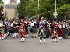 Massed Pipe Bands marching through Forres after the Highland Games - Drum Major tossing and catching his Mace.