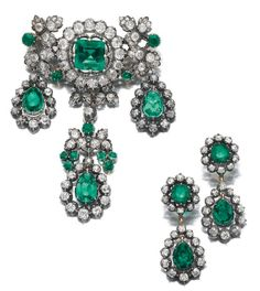 SUITE OF EMERALD AND DIAMOND JEWELS, LATE 19TH CENTURY  Comprising: a brooch decorated with foliate motifs set with cushion-shaped, circular-, single-cut and rose diamonds, accented with cushion-shaped emeralds, suspending three pampilles set with three pear-shaped emeralds  and a pair of swing-set emerald and diamond earrings en suite.