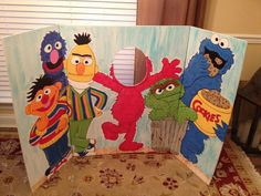 Paint 3, 2-fold cardboard display boards. Could put 3d trash can in front instead. Cut faces out of bert, ernie, cookie monster.