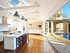Sliding french doors completely open the kitchen to the pool area - love this idea