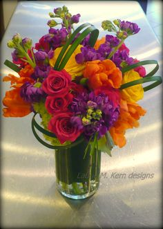 Add grass loops to a hand-tied bouquet and place in a vase lined with a large tropical leaf