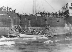 """Aliyah Bet (""""illegal"""" immigration) ship """"Parita,"""" carrying 850 Jewish refugees, lands on a sandbank off the Tel Aviv coast. The British arrested the passengers and interned them at Atlit detention camp. Palestine, August 21, 1939."""