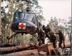Color photo of American 4th Battalion, 173rd Airborne Brigade soldiers loading wounded onto an UH-1D Huey helicopter being evacuated from Hill 875 15 miles southwest of Dak To during the Vietnam War. Description from amazon.com. I searched for this on bing.com/images