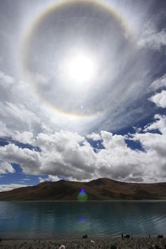 Tibetan Halo by Alan Millar - The particularly colorful halo featured above was snapped at Yamdrok Tso Lake, Tibet on October 29, 2011. This is a 22-degree halo -- the radius of the inner ring to the Sun. It's the most frequently observed of the circular halos. Randomly oriented, hexagonal ice crystals in cirrus clouds are responsible for its formation