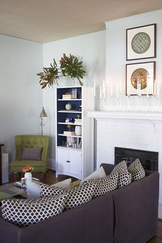 couch with no back cushions & pillows instead. love the bookcase w/painted shelf backs and green chair too! - great way to update that sofa that has smashed back cushions without replacing the whole sofa.