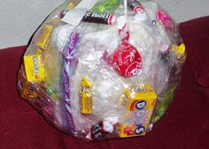 used masking and duct tape on the inside and clear packaging tape on the outside.  It really is simple make a ball of tape with prizes taped inside, small toys and candy.  (When we do this for holidays we put in money, giant pairs of underwear that sort of thing).  Have everyone who is playing get in a big circle, one player gets the tape ball and the player in front of them a pair of dice.  The player with the ball removes tape as fast as they can and anything they dislodge is theirs to keep...