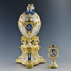 Russian Imperial Royal Danish Jubilee Egg is surmounted by a Danish Royal Elephant and supported by 3 danish heraldic lions, the white enameled egg is marked by diamond-set imperial crown.  At the center it has the crowned monogram of Tsarina Mariya name, emblazoned in rose-cut crystals. The double-sided miniature photo frame surmounted by a crystal crown is fitted inside.    The egg was gifted by Russian czar Nicholas to his wife Mariya Fyodorovna in 1903.